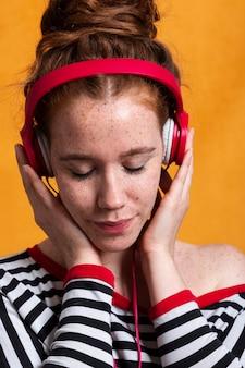 Close-up mulher com cabelo bun e fones de ouvido