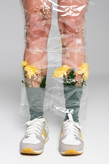 Close-up mulher com flores em meias cobertas de plástico