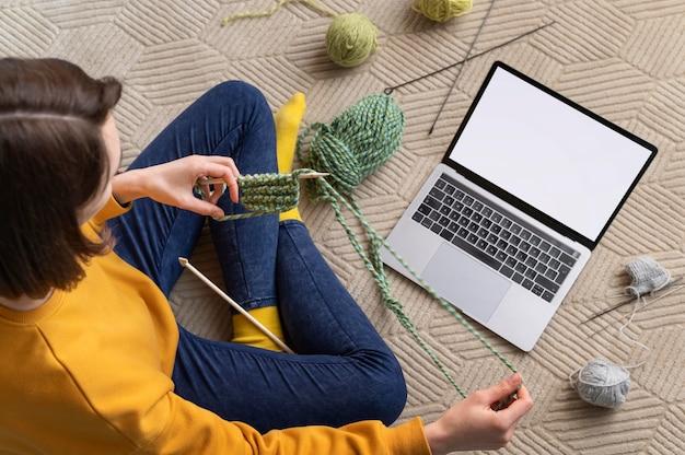 Close-up mulher com laptop tricotando