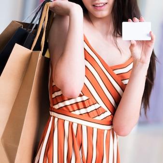 Close-up mulher com sacos segurando um cartão