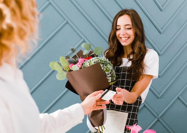 Close-up mulher comprando buquê de flores