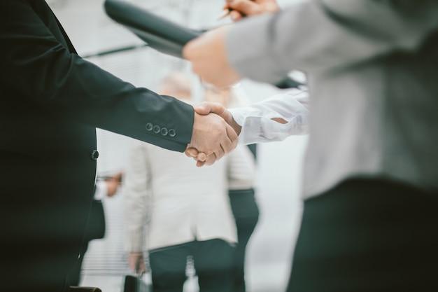Close-up mulher de negócios encontrando um colega com um aperto de mão