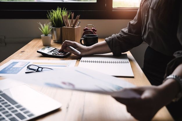 Close-up mulher de negócios usando a calculadora para fazer finanças matemática na mesa de madeira no escritório