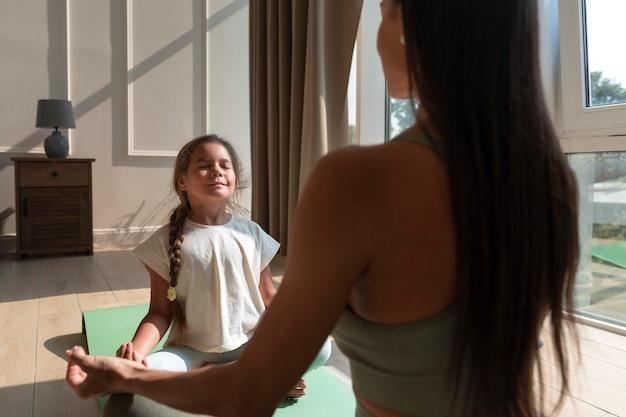 Close-up mulher e criança meditando
