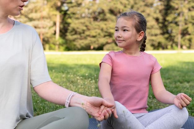 Close-up mulher e menina meditando