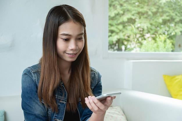 Close-up, mulher, em, calças brim azul, casaco, mantenha telefone móvel, ao lado, janelas