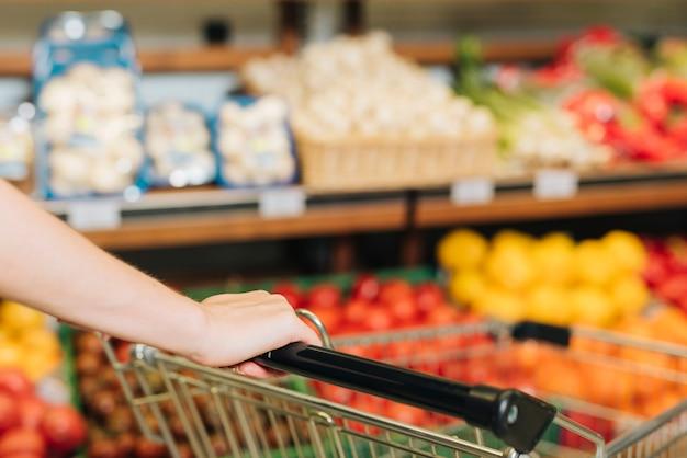 Close-up mulher empurrando um carrinho de compras