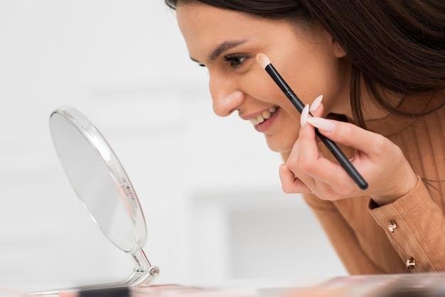 Close-up mulher fazendo maquiagem
