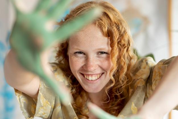 Close-up mulher feliz com as palmas das mãos pintadas