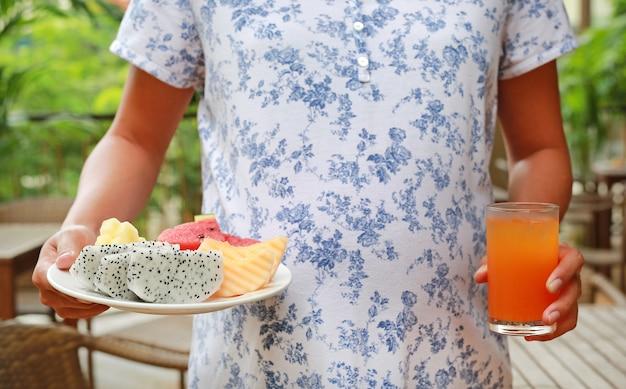 Close-up mulher grávida segurando frutas no prato e copo de suco de laranja