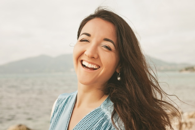 Close-up mulher jovem feliz perto do oceano, férias de verão