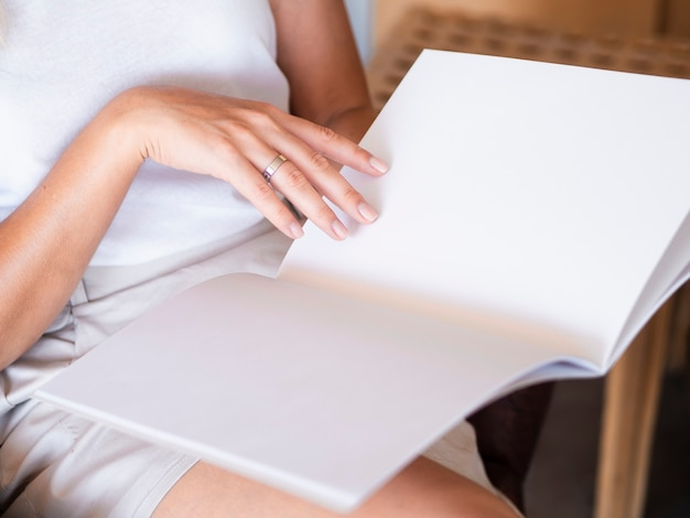 Close-up mulher lendo uma revista de maquete