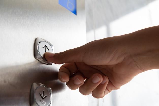 Close-up mulher mão pressione um botão de elevador dentro do edifício
