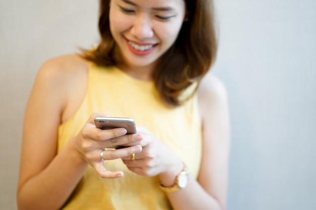 Close-up mulher. mão segure o dispositivo de telefone celular móvel