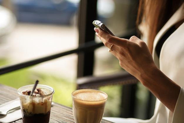 Close-up mulher mãos está conversando no telefone enquanto está sentado em um café com uma xícara de café e sobremesa