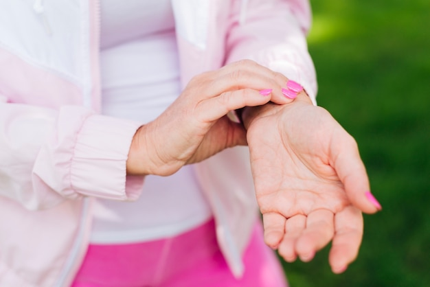 Close-up mulher medir seu pulso ao ar livre