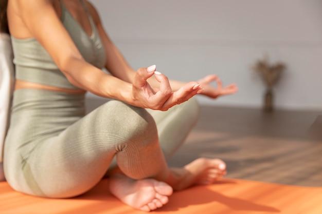 Close-up, mulher meditando no tapete de ioga