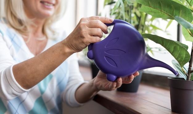 Close-up mulher molhando uma planta dentro de casa