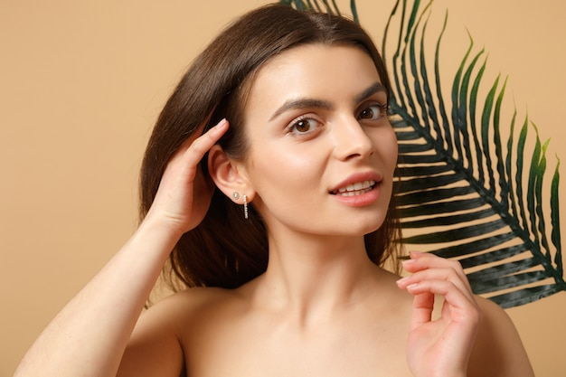 Close-up mulher morena seminua com pele perfeita, maquiagem nude e folha de palmeira isolada na parede bege pastel