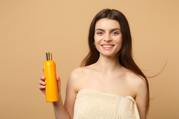 Close-up mulher morena seminua com pele perfeita, maquiagem nude isolada na parede bege pastel