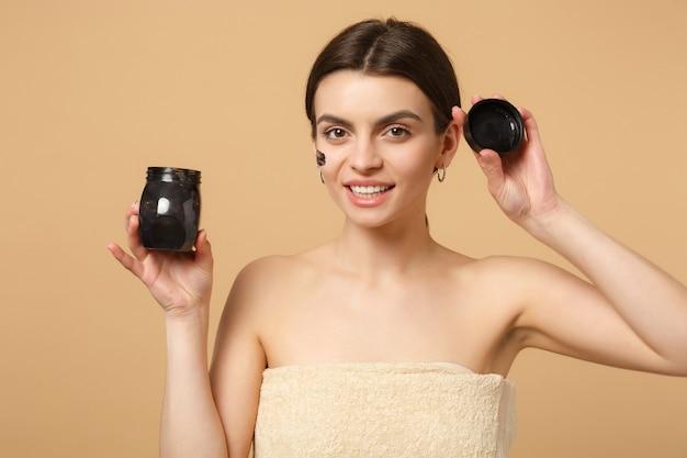 Close-up mulher morena seminua com pele perfeita, maquiagem nude máscara preta isolada na parede bege pastel