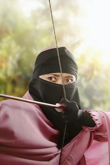 Close-up mulher muçulmana asiática com arco pronto para atirar uma flecha