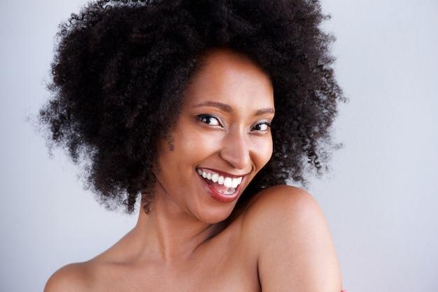 Close-up mulher negra com ombros nus, sorrindo em fundo cinza