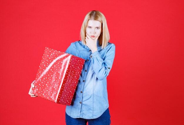 Close-up mulher pensativa segurando uma caixa de presente e mantendo a mão no rosto