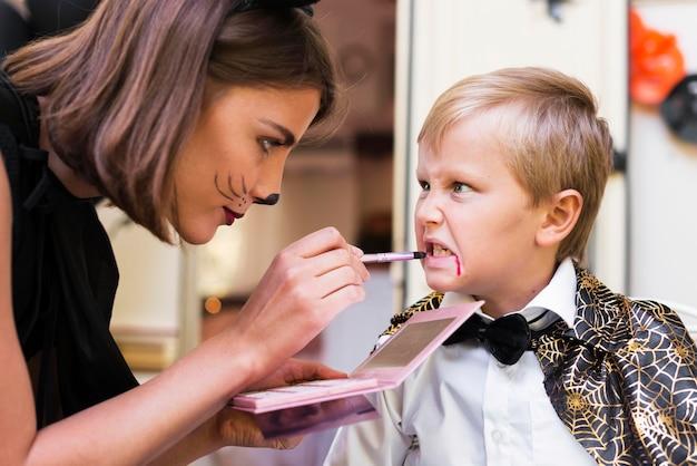 Close-up mulher pintando rosto de criança