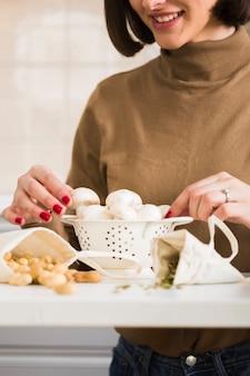 Close-up mulher preparando cogumelos caseiros