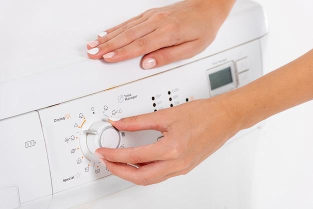 Close-up mulher programando a máquina de lavar roupa