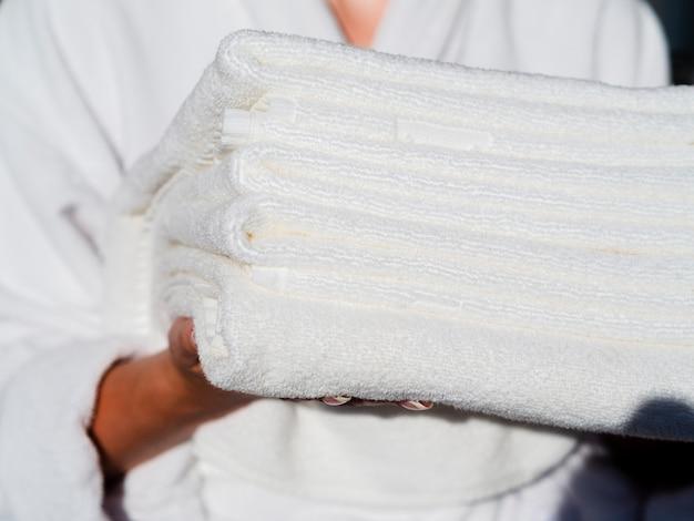 Close-up, mulher, segurando, branca, dobrado, limpo, toalhas
