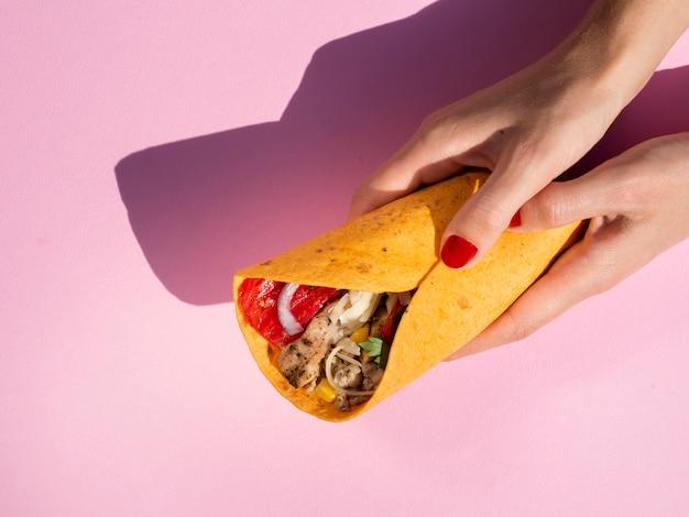 Close-up mulher segurando burrito com fundo rosa