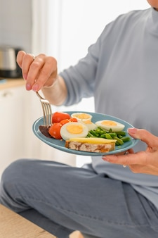 Close-up, mulher segurando café da manhã saudável com ovos cozidos e legumes no vapor no prato equilibrado