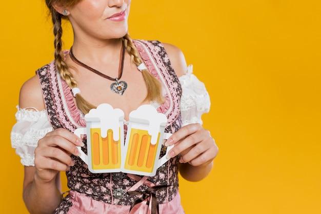 Close-up mulher segurando canecas de cerveja