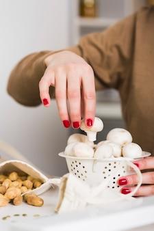 Close-up mulher segurando cogumelos frescos
