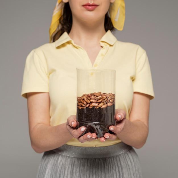 Close-up, mulher segurando frasco de plástico com feijão plantado