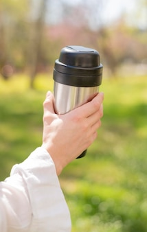 Close-up mulher segurando garrafa térmica na natureza