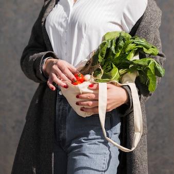 Close-up mulher segurando legumes orgânicos