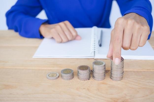 Close-up mulher segurando moeda com pilha de dinheiro e livro, caneta na mesa de madeira