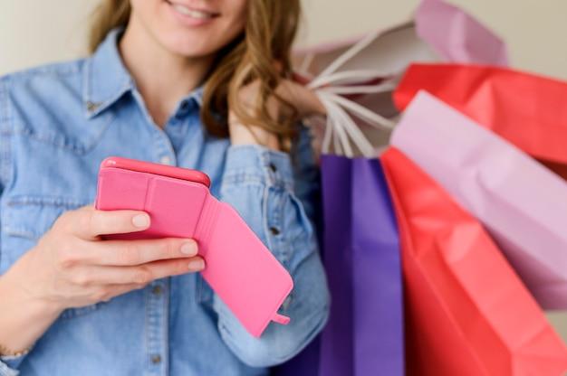 Close-up mulher segurando sacolas de compras