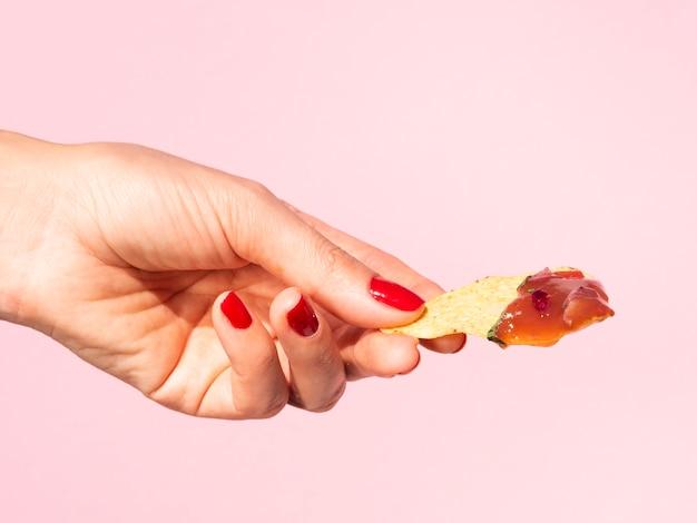 Close-up mulher segurando tortilla chips com fundo rosa