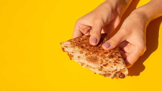 Close-up mulher segurando tortilla com fundo amarelo