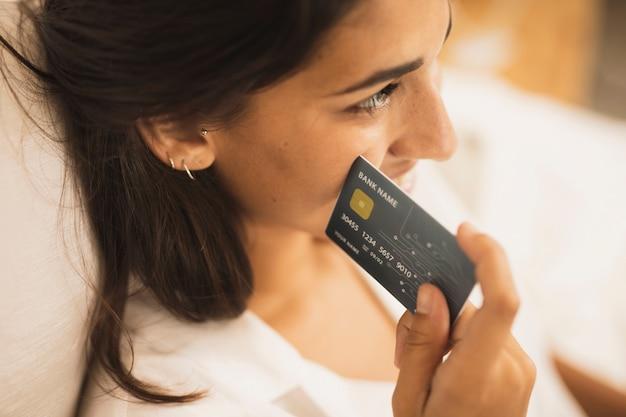 Close-up mulher segurando um cartão de crédito ao lado de sua bochecha