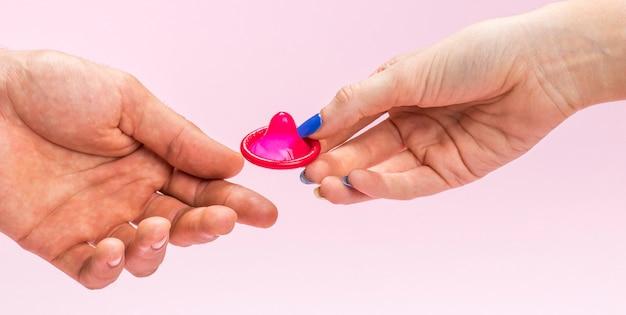 Close-up mulher segurando um preservativo vermelho
