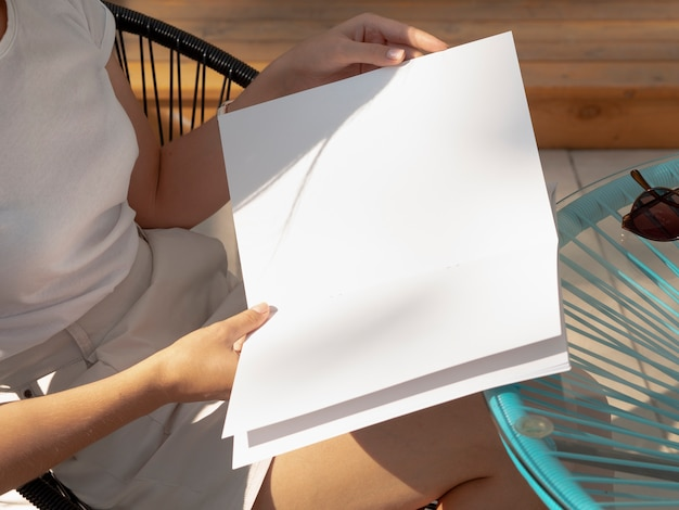 Close-up mulher segurando uma revista de maquete