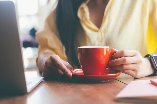 Close-up mulher segurando uma xícara de café vermelha