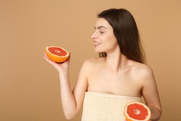 Close-up mulher seminua com pele perfeita maquiagem nude segura toranja isolada na parede bege