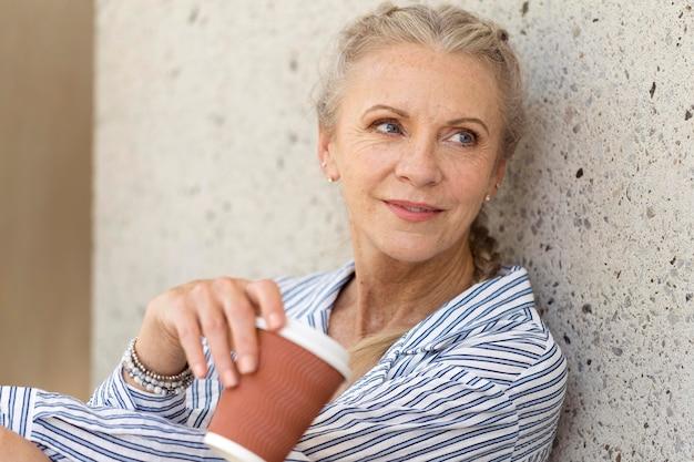 Close-up mulher sênior com uma xícara de café
