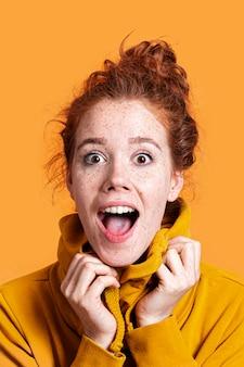 Close-up mulher surpreendida com fundo laranja